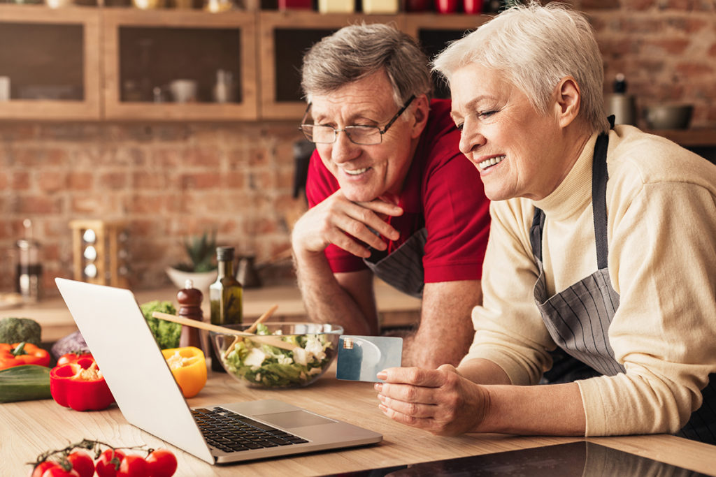 Happy seniors ordering Groceries online on laptop and credit card at kitchen